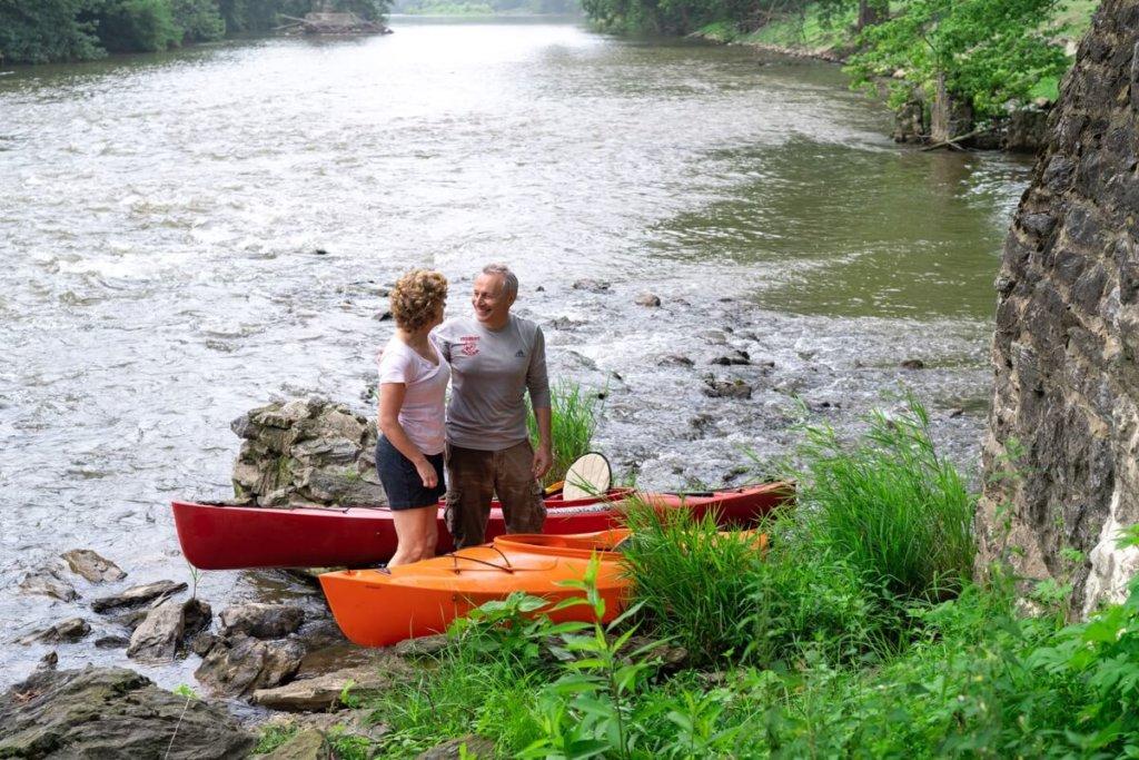 older couple smiling after kayaking on a creek